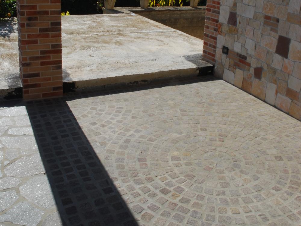Pavimentazione con cubetti di porfido lavorato a rosone centrale e coda di pavone laterale
