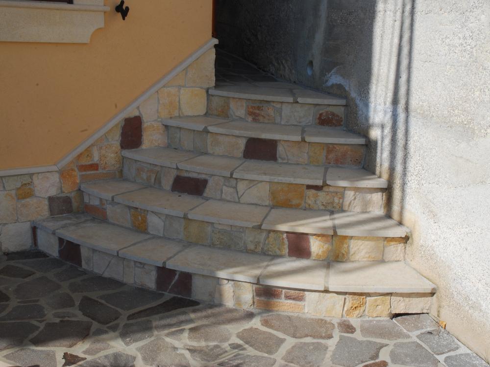 Scala con pedata in pietra di modica antichizzata e frontalino in pietra locale mista