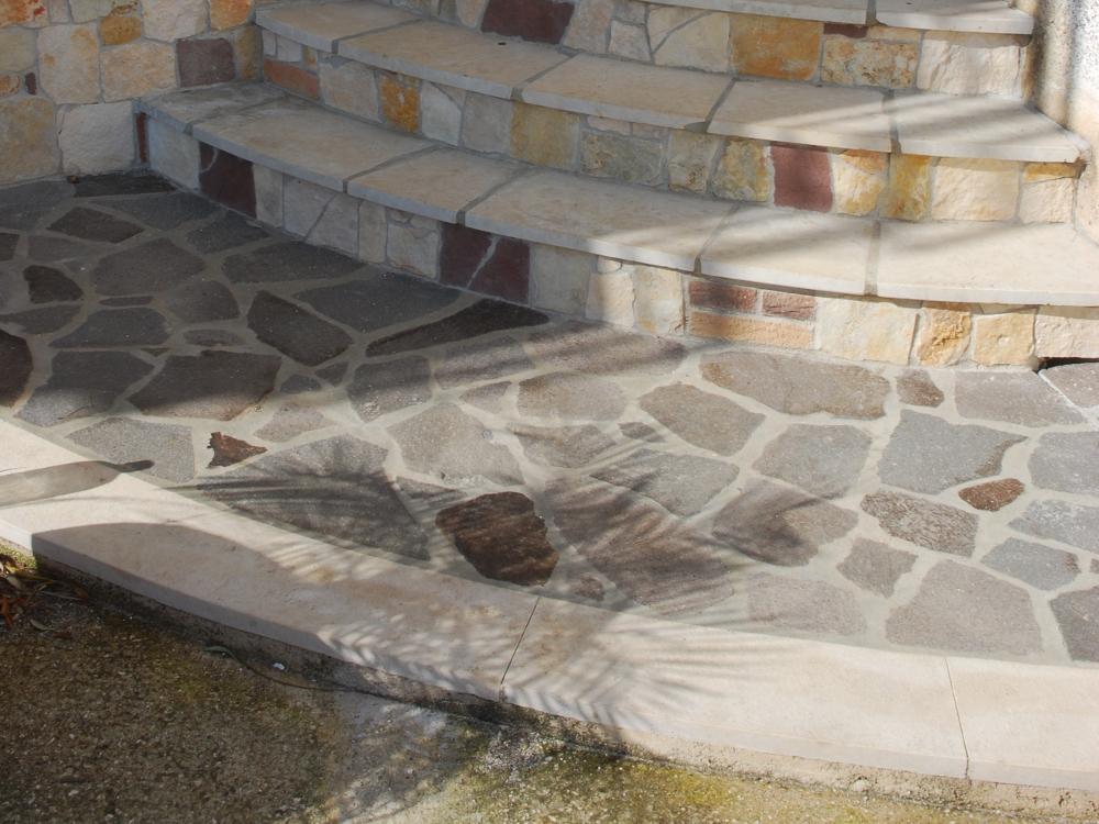 Pavimentazione opus incertum in porfido e fascia in pietra di modica antichizzata