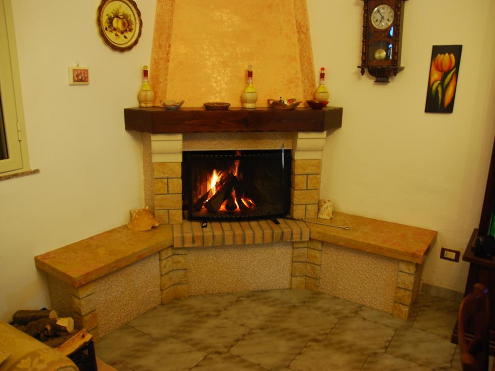 Focolare aperto - Rivestimento WILD WEST: base con marmo giallo reale, pannelli in pietra di trani picconata, mattoncini in cotto e capitelli in pietra di modica. Legno col. Noce sfumato antichizzato